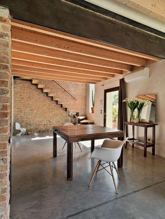Innenansicht eines Esszimmer mit Blick auf den Eingang mit Betonboden, Holzdecke und staicase in einer rustoc Villa
