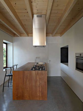 interior view of a modern kitchen with wooden island , wood ceilinf and concrete floor