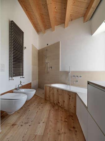 Innenansicht eines modernen Bades mit Holzdecke und Holzboden