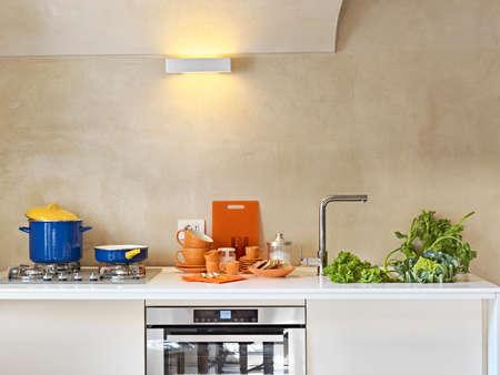 pans, dishes and vegetables on the worktop in the modern kitchen Lizenzfreie Bilder