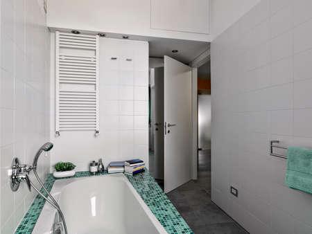 Innenansicht eines modernen Badezimmers im Vordergrund der Badewanne mit Mosaik-Fliesen und whte Heizkörper