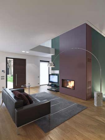 Innenansicht eines modernen Wohnzimmer mit Ledersofa und Teppich vor dem Kamin auf Tmain Tür, deren Boden mit Blick ist aus Holz Lizenzfreie Bilder