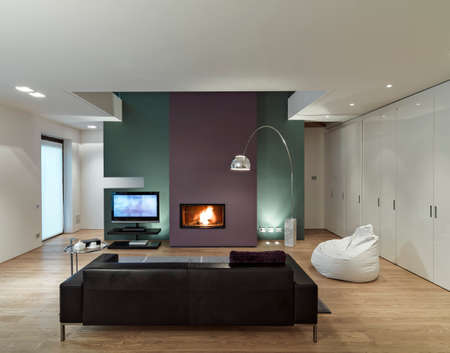 interior view of a modern living room with leather sofa in front of the fireplace  whose floor is made of wood