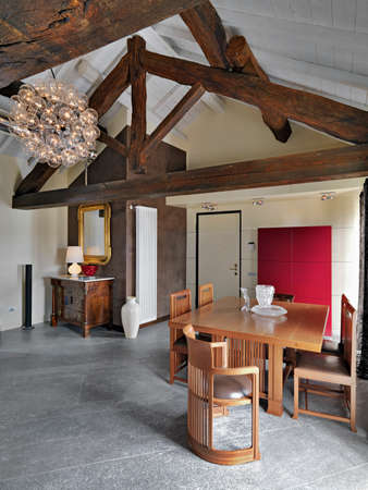 furnishings: dining table on entrance of a attic with trused roof and ancient chest  of drawers