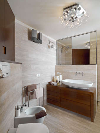 furnishings: interior view of a modern bathroom, in foreground the wood furniture with washbasin whose walls  are  coated of marble