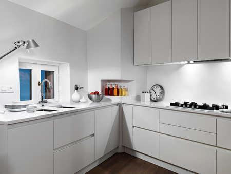 interior view of a white  modern kitchen in the mansard with wood floor Lizenzfreie Bilder