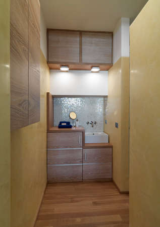 Innenansicht eines modernen Badezimmers im Vordergrund des Waschbeckens der Boden ist aus Holz