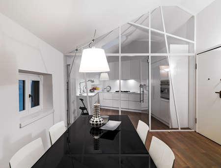 Innenansicht eines modernen Wohnzimmers im Vordergrund der Esstisch mit Blick auf die Küche, deren Boden aus Holz Lizenzfreie Bilder