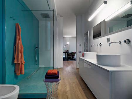 Innenansicht eines modernen Badezimmers mit zwei Arbeitsplatten Weshvasin mit Duschkabine und Holzboden