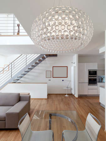 interior view of a modern living room in foreground the dining table and glass chandelier whose floor is made of wood in baclground the stairs Standard-Bild