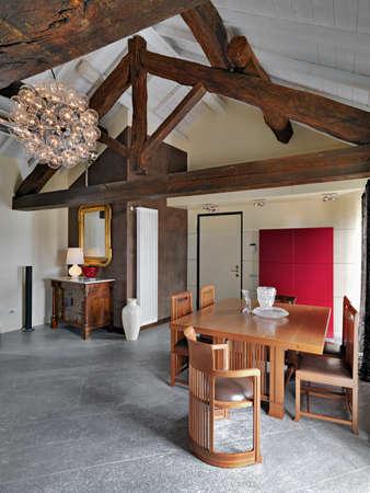 Esstisch am Eingang eines Dachbodens mit Trümmerdach und antiker Kommode