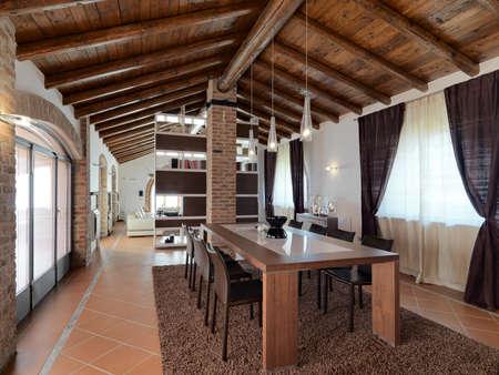 foregorund von einem Esstisch in einem modernen Wohnzimmer im Penthouse mit Terrakotta-Fliesen und Holzdecke mit Blick auf das Sofa