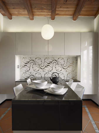 dishes in foreground on the dining table  in the modern kitchen whose floor is made of terracotta tiles