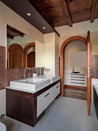 Innenansicht des modernen Badezimmers im Vordergrund der Waschtisch der Boden ist aus Fliesen