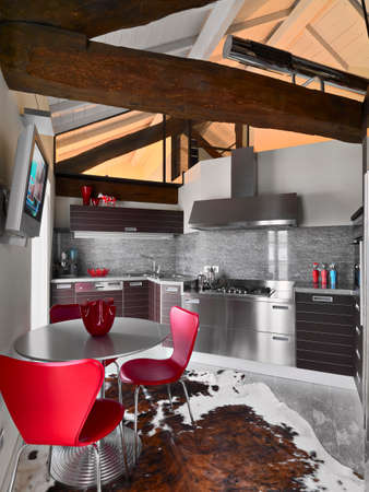 Interiors shots of a modern kitchen in the mansard with trusses and carpet under the dining table