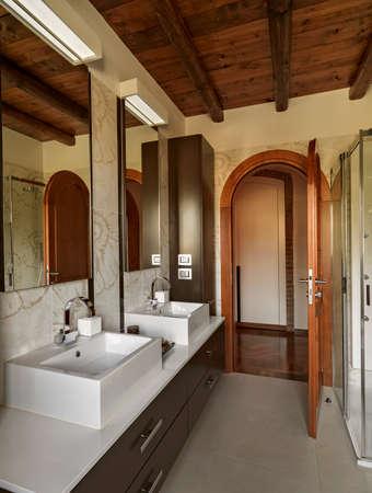 Interiors Aufnahmen von einem modernen Badezimmer im Vordergrund zwei Waschbecken, deren Boden aus Fliesen und die Decke ist aus Holz Lizenzfreie Bilder