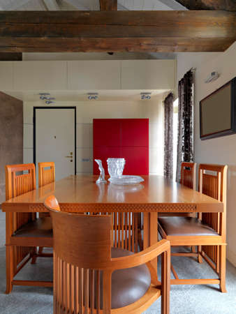 Interiors shots of a modern living room in the foreground the dining table with chairs in the mansard