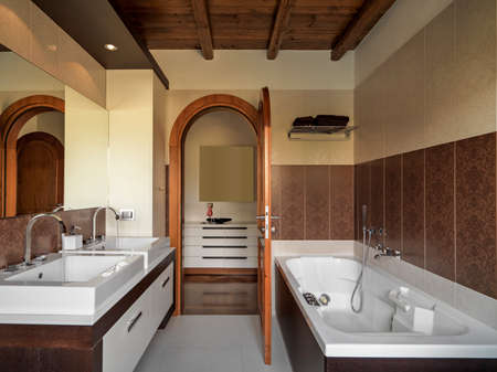 Interiors shots of modern bathrooms in foreground two counter top washbasin and the bathtub overlooking the wooden door opened on the corridor