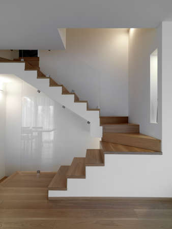 internal shots of a modern living room  in foreground the wooden staircase whose floor is made of wood Stock fotó