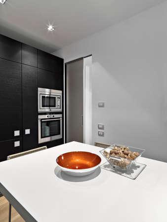 Innenaufnahmen einer modernen Küche im Vordergrund die Glasschale voller Haselnüsse auf dem Boden der eingebaute Stahlofen Lizenzfreie Bilder