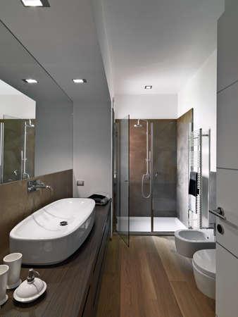scatti interni di un bagno moderno il cui pavimento è in legno in primo piano il lavabo da banco sui mobili in legno nel fondo il box doccia in muratura con porta in vetro e la vasca da bagno e bidet