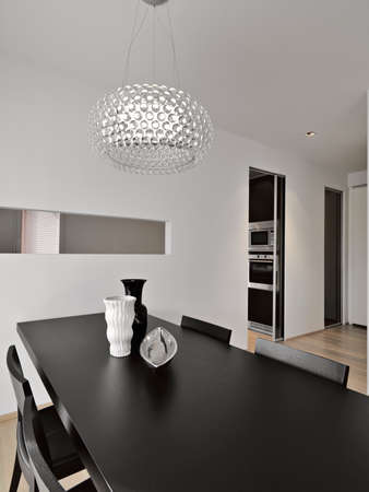interiors shots of a modern dinin room in foreground the vase of ceramic on the wood dining table and the glass modern chandelier on the bottom the kitchen