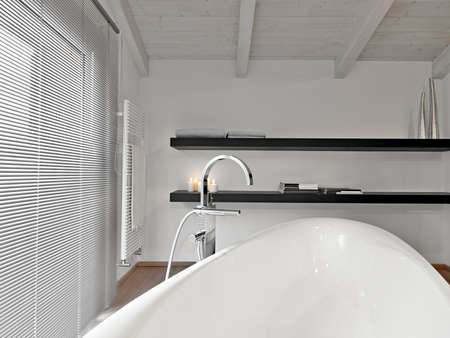 interiors shots of a modern bathroom in the attic room in foreground the bathtub and steel water tap in the bottom two wooden shelfs