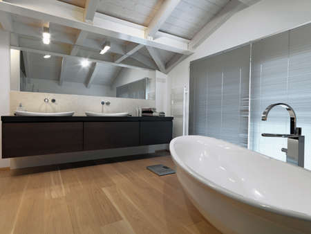 penthouse: interiors shots of a modern bathroom in the attic room with wooden ceiling and wood floor two counter top on the wooden plan and the bathtub in the center