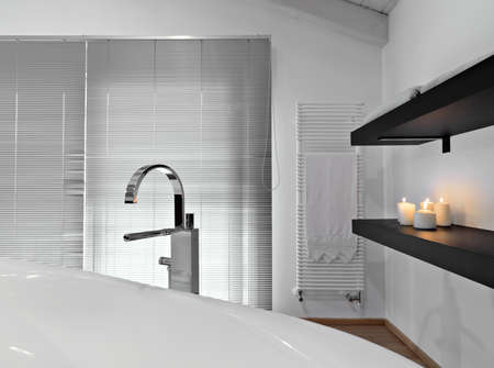 interiors shots of a modern bathroom in foreground the water tap of the bathtub Standard-Bild