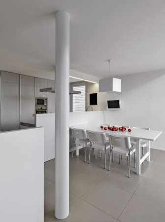 internal shot of a modern dinner room overlooking on the kitchen with several red apples on the table