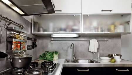 interiors shots of a modern kitchen in the foreground the gas hob and the steel sink Standard-Bild