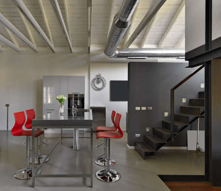 Interior view of a modern dining room in the foreground of the iron table with built-in washbasin and around there are the red stools Standard-Bild