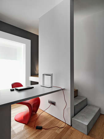 interiors shots of a modern workplace with a modern writing desk near to masonry staircase the floor is made of wood