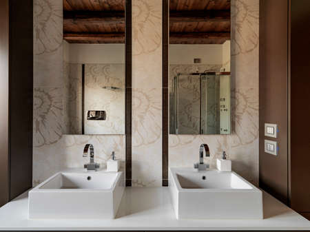 interior view of modern bathroom in foreground two washbasin the    floor is made of tiles