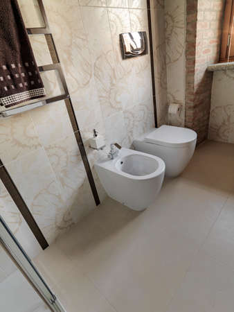 interior view of a modern bathroom in foreground the bidet whose floor is made of tiles Standard-Bild