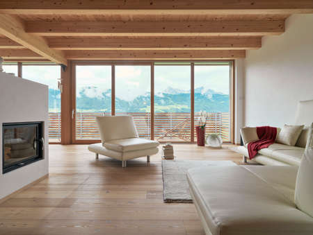 Interiors shots of a living room with a modern leather sofas and the fireplace the floor and the ceiling are made of wood overlooking on the mountain landascape