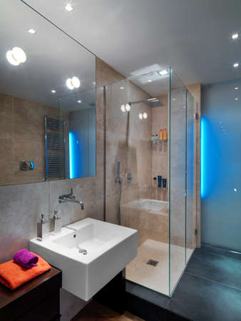 interiors shots of a modern bathroom in the foreground the counter top washbasin in the bottom the glass shower cubicle