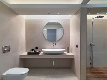 interior view of a modern bathroom in foreground the countertop washbasin wohse walls are coated of pink marble overlooking on the shower cubicle Stock fotó