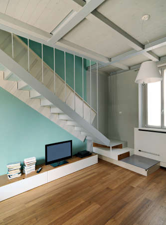 interiors  shots of a modern living room in the foreground the contemporary iron and wood staircase the floor is made of wood Archivio Fotografico