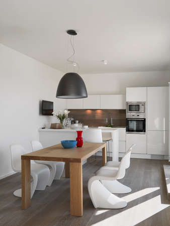 interior shot of a modern kitchen in the foreground the wooden with plastic chairs and  the dining table on the background the white kithen with kitchen island, the floor is made of wood