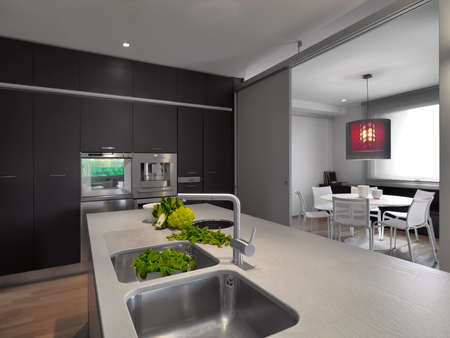 interiors shots of a modern kitchen with kitchen island in the foreground the wirktop and steel sink integrated on hte background the dining table Stock Photo