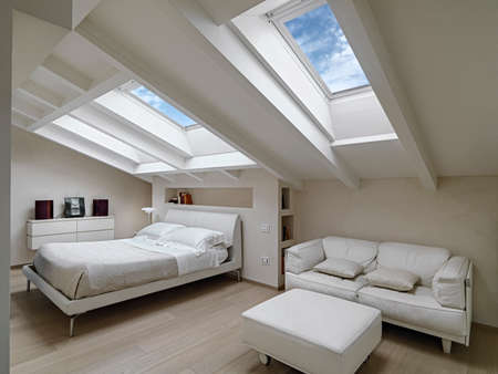 interior shot of a bedroom in the modern attic-room in the foreground the leather sofas with footrest in the background there is the bed illuminated by two skylights