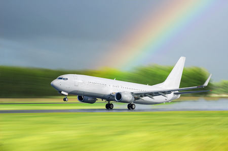Airplane Airport take off in the rain on a background a rainbow Stock Photo