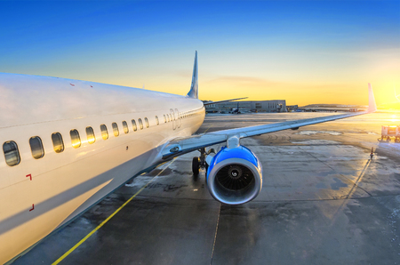 Airplane view of the passenger at the entrance, sunrise and parking in the airport engine Stock Photo