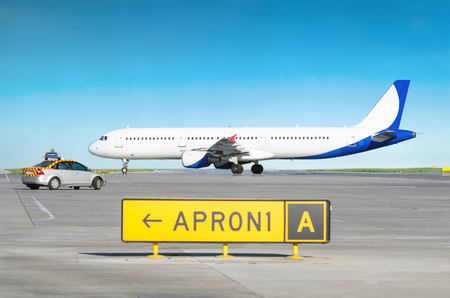 Aircraft at the airport after landing and the airport service car with the inscription follow me. Stock Photo