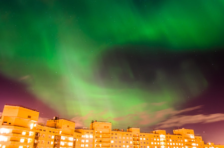Aurora borealis green starry night over the city and houses. Stock Photo