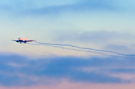 Airplane comes in approach at the airport before landing through the clouds at sunset.