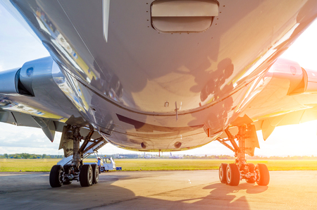 Large modern airplane view from bottom to bottom and landing gear, light sun.