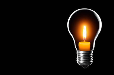 Lamp bulb inside a candle on a black background, with space for text. Stock Photo
