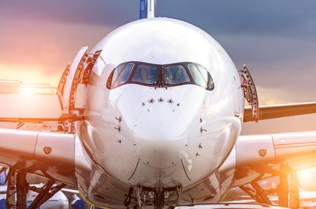 공항에서 석양 앞 콕핏 동체에서 비행기보기. 스톡 콘텐츠
